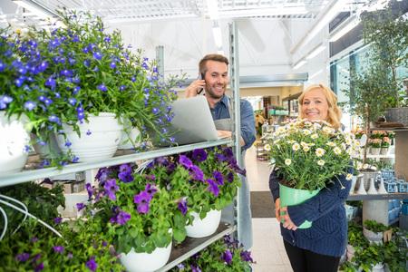 Ritratto di cliente femminile con vaso di fiori in piedi dal fiorista con il cellulare in negozio photo
