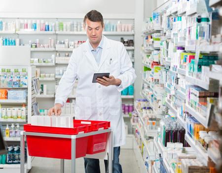 La metà degli adulti di sesso maschile farmacista contando magazzino mentre si utilizza tavoletta digitale in farmacia photo