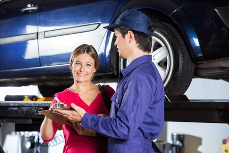 two car garage: Portrait of happy female customer signing document while standing with technician in garage Stock Photo