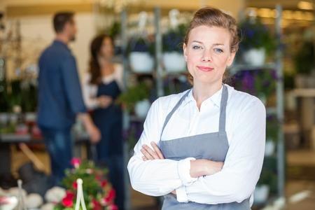 mid adult female: Portrait of confident mid adult female proprietor at flower shop