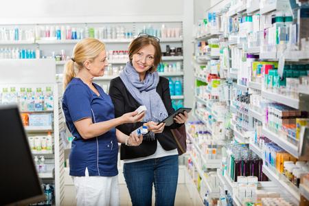 Ritratto di donna in piedi al cliente dal farmacista mostrando le medicine in farmacia photo