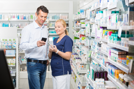 Sorridente metà degli adulti di sesso maschile informazioni dei clienti mostrando prodotto su telefono cellulare per il farmacista in farmacia photo