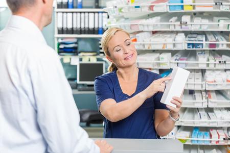 Sorridente farmacista femminile che mostra i dettagli del prodotto al cliente in farmacia photo