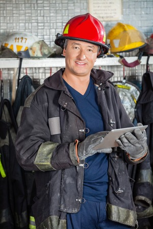 Ritratto di sorridere maturo vigile del fuoco in uniforme che tiene tavoletta digitale alla stazione di fuoco photo