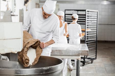 flour: panadero macho maduro vertiendo la harina en la máquina de amasar en la panadería Foto de archivo