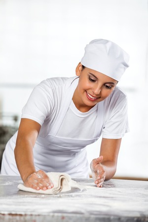 Smiling female baker cleaning table in bakery