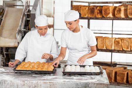 Giovani colleghi femminile che prepara pane insieme a tavola in forno photo