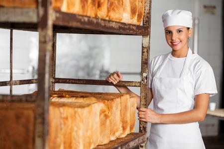 Ritratto di fiducia panettiere femminile in piedi dalla cremagliera pane in panetteria photo