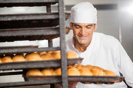 removing: Smiling male baker removing baking tray from rack in bakery Stock Photo