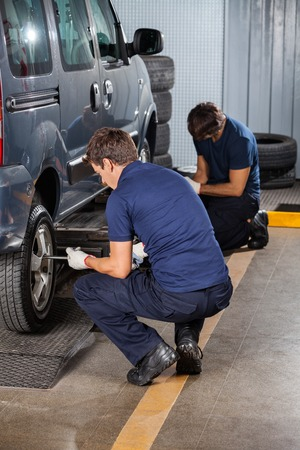 auto repair: Male mechanics fixing car tires at auto repair shop
