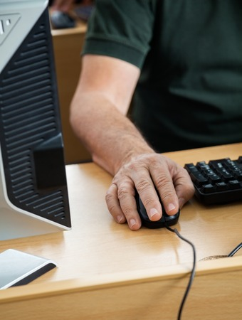 Midsection of senior male student using desktop PC in classroom