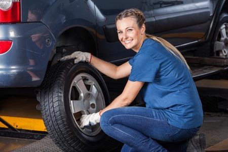 auto repair: Portrait of smiling female technician adjusting car tire at auto repair shop
