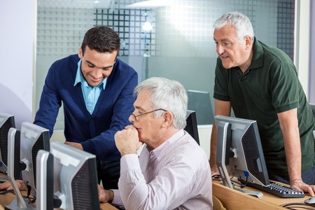 the elderly tutor: Happy young male instructor explaining senior men in computer class