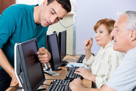 Giovane tutore maschio guidare gli studenti anziani in utilizzando il computer in aula