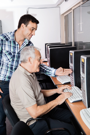 the elderly tutor: Male tutor assisting senior man in using computer at classroom Stock Photo