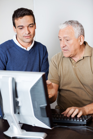 the elderly tutor: Senior man communicating with male teacher while pointing towards computer monitor in class Stock Photo