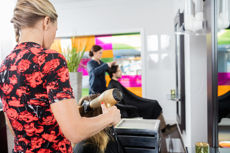 blow dryer: Hairstylist drying customers hair with blow dryer in beauty salon Stock Photo