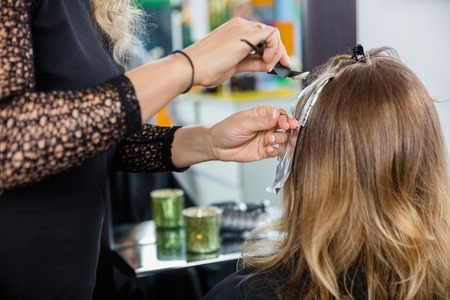 hairtician: Cropped image of hairdresser highlighting female clients hair in salon Stock Photo