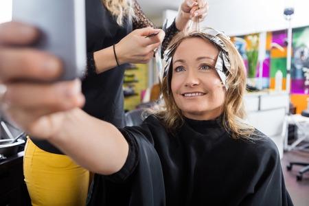 tinte cabello: Cliente feliz madura autofoto hablar mientras se pone de relieve el pelo en salón de belleza