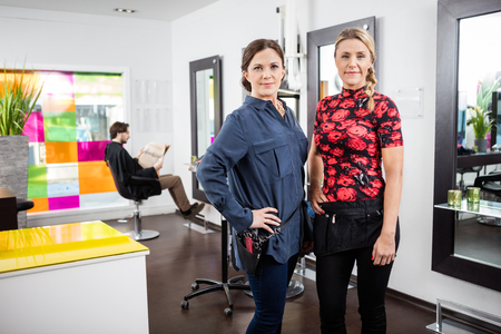 Portrait of confident female hairdressers with male client in background at salon Stock Photo