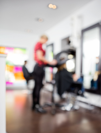 parlor: Defocused image of female hairdresser with customers in salon Stock Photo