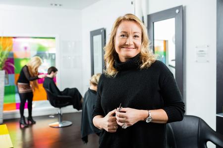 Confident female hairdresser holding scissor while standing in salon