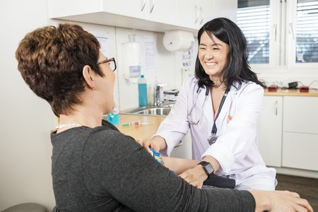 work checkup: Happy female doctor adjusting band on patients hand in clinic