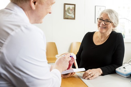 man doctor: Happy senior patient looking at male doctor explaining shoulder rotator cuff model in clinic Stock Photo
