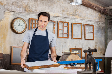 paper factory: Portrait of confident worker holding mold at paper factory Stock Photo