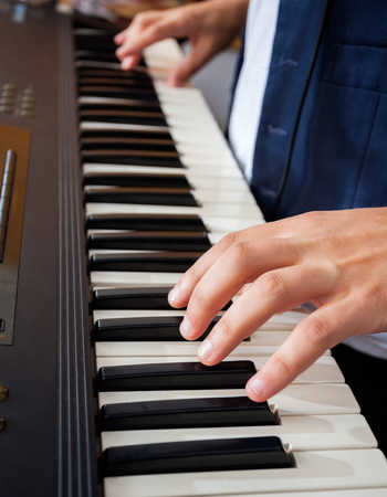 keyboards: Closeup of mans hands playing piano in recording studio Stock Photo