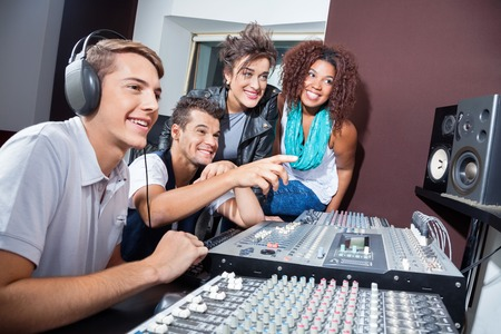 masters of rock: Happy multiethnic musicians mixing audio together at table in recording studio