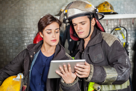 fire fighting equipment: Young firefighters using digital tablet at fire station