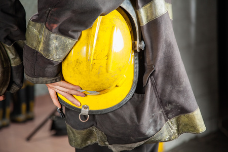 firefighting: Midsection side view of female firefighter holding yellow helmet at fire station