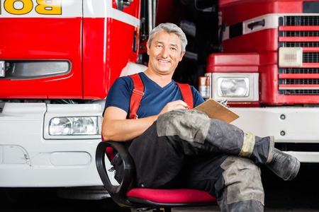 firefighting: Full length portrait of smiling firefighter sitting on chair against trucks at fire station Stock Photo