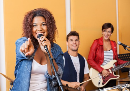 musical band: Portrait of passionate female singer pointing while performing in recording studio