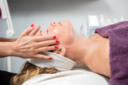 beauty parlor: Side view of mature woman receiving facial massage in beauty parlor