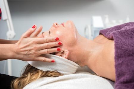 Zijaanzicht van volwassen vrouw ontvangt gezicht massage in de schoonheidssalon Stockfoto