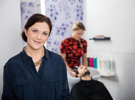hairstylist: Portrait of beautiful hairstylist with female associate washing customers hair in background
