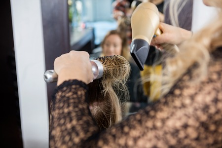 blow dryer: Cropped image of hairdresser styling female customers hair with blow dryer and brush in salon