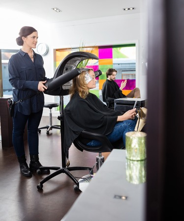 hairstylist: Hairstylist adjusting drying accelerator over female customers head in salon