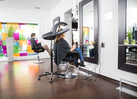 Male and female customers undergoing hair treatment in salon Stock Photo