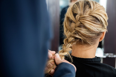Cropped image of hairdresser braiding client's hair in salon