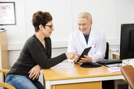 communicating: Mature female patient and male doctor communicating over digital tablet in clinic Stock Photo