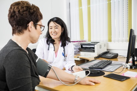 mid adult   female: Happy mid adult female doctor looking at patient while examining her blood pressure in clinic