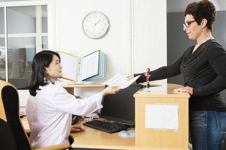 Mature female patient giving reports to doctor in office
