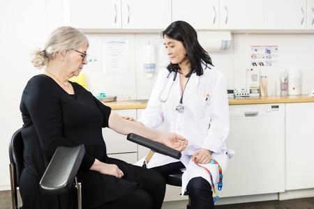 conclusion: Mediados médico adulto tocando el brazo de paciente de alto nivel antes de la prueba de sangre en la clínica Foto de archivo