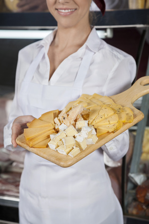 delicatessen: Midsection of young saleswoman holding cutting board with assorted cheese in store