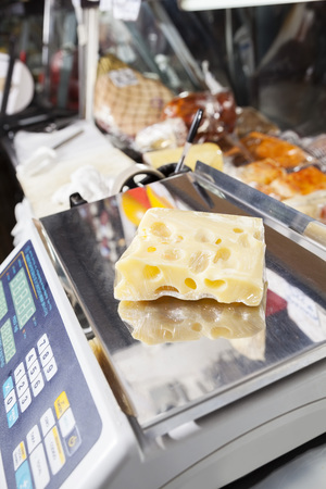 food shop: Closeup of packed cheese on weight scale in store Stock Photo