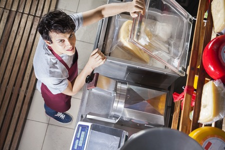 High angle portrait of young salesman packing cheese in vacuum machine at grocery store Stok Fotoğraf