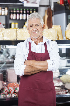 artisan: Portrait of confident senior salesman standing arms crossed in grocery store